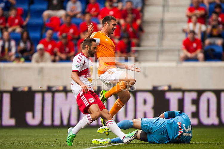 Will Bruin (12) of the Houston Dynamo jumps over New York Red Bulls goalkeeper Luis Robles (31) during a Major League Soccer (MLS) match at Red Bull Arena in Harrison, NJ, on June 30, 2013.