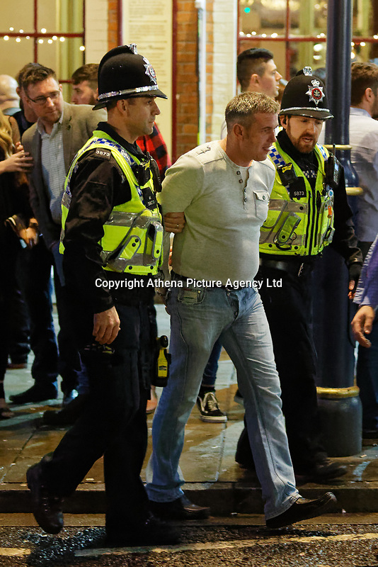 Police officers escort a man away from Wind Street, Swansea, Wales  on Mad Friday, Booze Black Friday or Black Eye Friday, the last Friday night before Christmas Day, when traditionally people in the UK go out to celebrate the start of their holidays. Friday 22 December 2017