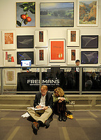 Art buyer Bob Apfell, left and Jai Imbrey, right, review the Freeman's auction house catalog prior to the bidding of the Lehman Brothers Corporate Art Collection November 1, 2009 in Philadelphia. (Bloomberg News/Bradley C Bower)