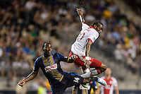 Amobi Okugo (14) of the Philadelphia Union and Frederic Piquionne (10) of the Portland Timbers get tangled up going for a header. The Philadelphia Union and the Portland Timbers played to a 0-0 tie during a Major League Soccer (MLS) match at PPL Park in Chester, PA, on July 20, 2013.