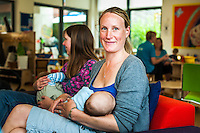 Portrait of a breastfeeding mother at a drop-in breastfeeding support centre, with another mother breastfeeding in the background.<br /> <br /> 01/06/2011<br /> Hampshire, England, UK