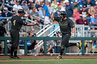 Vanderbilt Commodores outfielder Stephen Scott (19) celebrates with head coach Tim Corbin (4) after his second home run of the game against the Mississippi State Bulldogs in the NCAA College World Series on June 19, 2019 at TD Ameritrade Park in Omaha, Nebraska. Vanderbilt defeated Mississippi State 6-3. (Andrew Woolley/Four Seam Images)