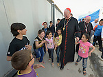 Cardinal Timothy Dolan, the archbishop of New York, is accompanied by children as he walks through a camp for internally displaced families in Ankawa, near Erbil, Iraq, on April 9, 2016. Dolan, chair of the Catholic Near East Welfare Association, led a delegation of church leaders to Iraqi Kurdistan in order to visit with Christians and others displaced by ISIS. <br /> <br /> Behind Dolan is Bishop William Murphy of Rockville Centre.
