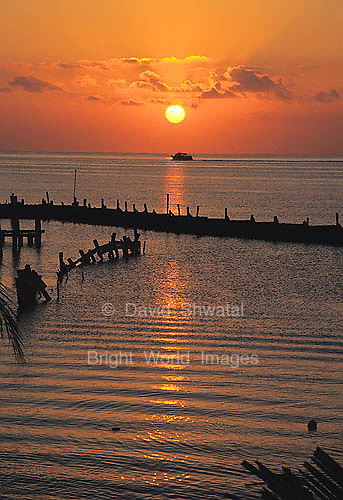 The sun rises over a pier as a ferry boat crosses the sea in Cancun Mexico