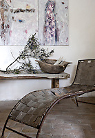 In a corner of the living room by the side of a rustic bench is an antique chaise longue upholstered in linen webbing