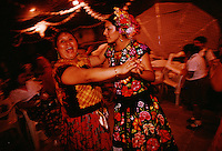 Zapotec Indian women in traditional clothing dance into the night at a wedding party in the street. Weekends are full of wedding celebrations in the Isthmus of Tehuantepec in Mexico, the narrow and flat part of the country where the Zapotec culture is still strong. <br /> Women are noticeably open and confident, taking a leading role in business and government. <br /> <br /> The Isthmus never became part of the Aztec Empire and resistance to the Spanish was strong in the mid-1500s.  This party was complete with traditional food and dancing. After the church wedding, the couple walks through the streets of town following musicians. They collect family and carry food to where the street is blocked off for the party.