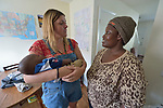 Monique Lohmeyer (left), a case manager for Church World Service, talks with Bashige Chichibanji while holding the sleeping son of a neighbor in the apartment of a Congolese refugee family that was resettled by her agency.<br /> <br /> Church World Service resettles refugees in North Carolina and throughout the United States.<br /> <br /> <br /> Photo by Paul Jeffrey for Church World Service.