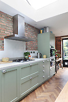Pale green units with white, Metro style wall tiles, artfully lined up with the existing bare-bricks of the walls
