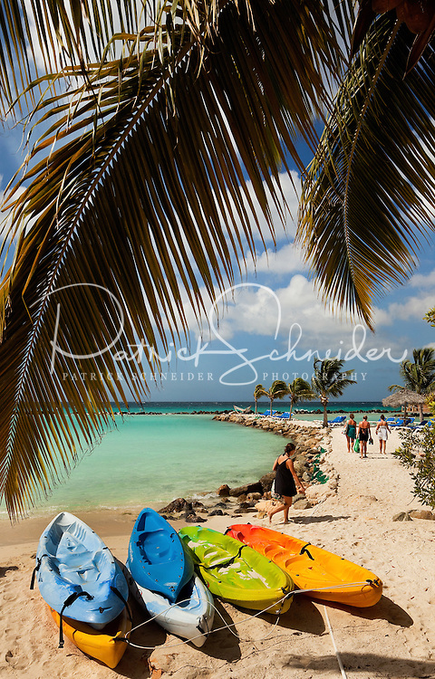 Kayaks rest in the sand on private Renaissance Aruba Island in the Caribbean Sea. Renaissance Island, owned by the Marriott chain of hotels, is about 40 acres large with two horseshoe shaped beaches protected from the Caribbean sea currents by rock breakers. Aruba remains a popular tourist destination, with international planes and cruise ships arriving daily. Aruba, part of the Lesser Antilles, is famous for its white sand beaches, blue/green waters and mild climate.
