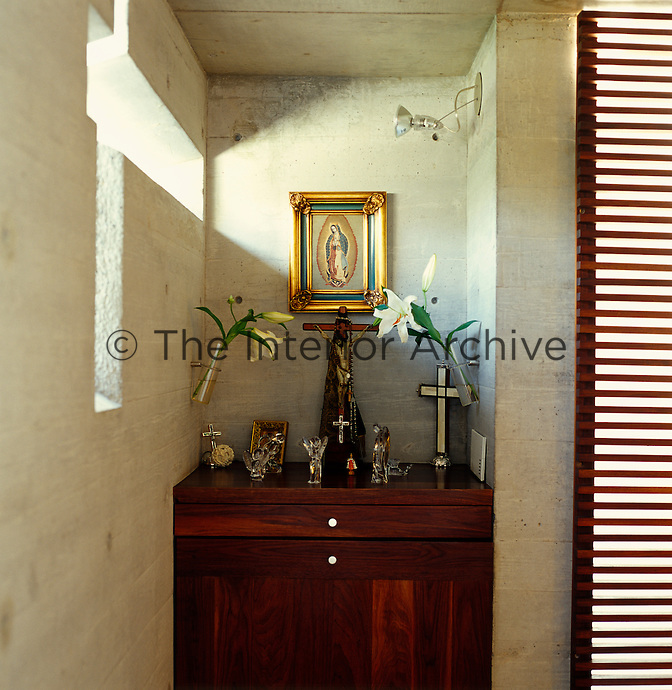Sunlight pours onto a shrine through a small window in the concrete wall