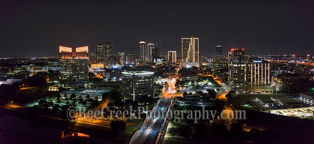 This panorama aerial image of Fort Worth cityscape was taken looking down seventh street bridge into downtown part of the city after dark.  The citys building were lighted up so you can see the high rise buildings in the downtown area.  The seventh street bridge connects the University area with the downtown and was a busy place on a saturday night.Fort Worth is the fifth largest city in Texas. Ft Worth is located in central north part of Texas and the county seat is Tarrant County. The latest census is that the population for Fort Worth is estimates, at around 854,113. The city is the second-largest in the Dallas–Fort Worth–Arlington metropolitan area or the DFW Metro.
