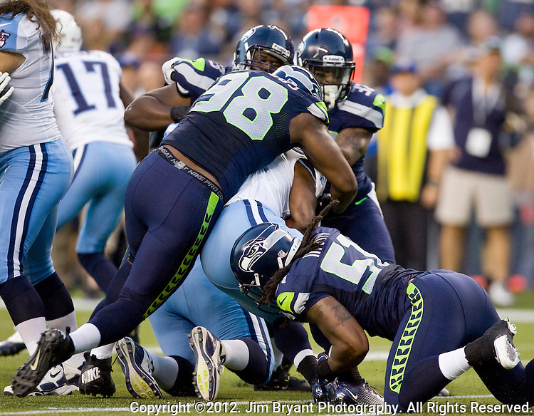 Seattle Seahawks' defenders Greg Scruggs (98), Bruce Irvin, Roy Lewis and Jeron Johnson gang tackle Tennessee Titans' running back Chis Johnson in a pre-season game at CenturyLink Field in Seattle, Washington on August 11, 2012. ©2012. Jim Bryant Photo. All Rights Reserved...