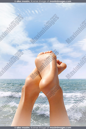 Woman on the beach with close-up of her feet in the air. Colorful expressive photo for summer vacation, environmental, recreational, healthcare concepts