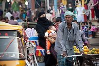 Muslim woman and child travel by rickshaw in crowded street scene in city of Varanasi, Benares, Northern India