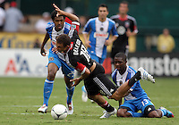 WASHINGTON, D.C. - AUGUST 19, 2012:  Nick DeLeon (18) of DC United is pulled down by Michael Lahoud (13) of the Philadelphia Union during an MLS match at RFK Stadium, in Washington DC, on August 19. The game ended in a 1-1 tie.