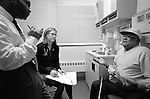 Young female internal medicine resident physician and Spanish translator listening to elderly African-American male in examination room