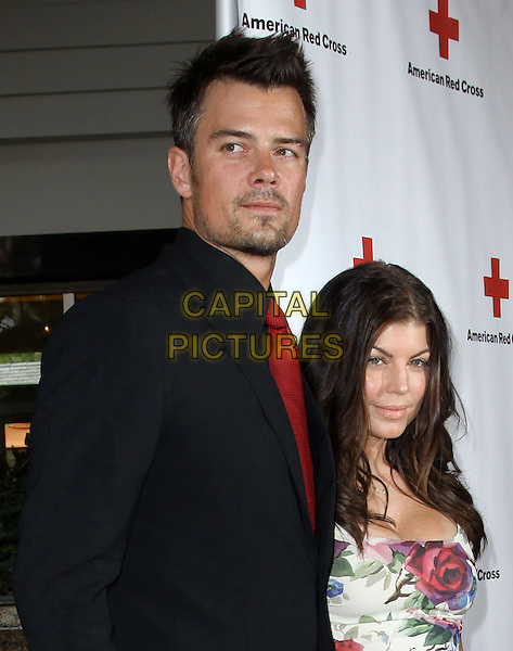 JOSH DUHAMEL & FERGIE (STACY FERGUSON).The American Red Cross Red Tie Affair Fundraiser Gala held At Fairmont Miramar Hotel, Santa Monica, California, USA, 17th April 2010..half length tall short  black suit red tie shirt couple husband wife married couple smiling rose floral white print beard facial hair stubble cleavage .CAP/ADM/KB.©Kevan Brooks/AdMedia/Capital Pictures.