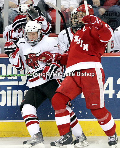 Wisconsin's Sean Dolan shoves UNO's Zahn Raubenheimer into the boards. No. 16 UNO beat No. 7 Wisconsin 4-3 Saturday night at Qwest Center Omaha. (Photo by Michelle Bishop)