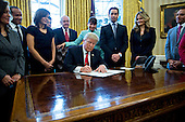 U.S. President Donald Trump signs an executive order in the Oval Office of the White House surrounded by small business leaders in Washington, D.C., U.S., on Monday, Jan. 30, 2017. Trump said he will dramatically reduce regulations overall with this executive action as it requires that for every new federal regulation implemented, two must be rescinded. <br /> Credit: Andrew Harrer / Pool via CNP