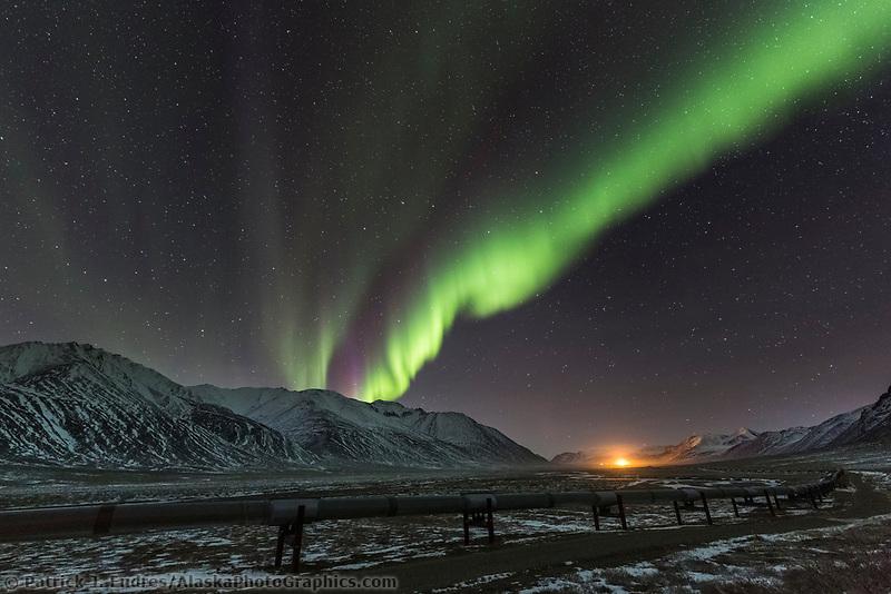 The northern lights over the Trans Alaska Oil Pipeline in Atigun Canyon, Alaska's Arctic.