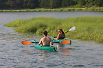 Man and woman kayaking in salt water marsh. Cape Cod, MA