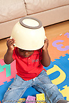 12 month old baby boy sitting on floor with bowl in his head peek a boo vertical