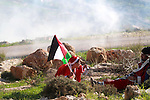 Palestinians, wearing Santa Claus costumes take cover from tear gas fired by Israeli soldiers during clashes in the West Bank village of Bilin, west of Ramallah, following a march organized in solidarity with the people of the village against the construction of settlements and the confiscation of their land on December 26, 2014. Photo by Shadi Hatem