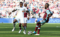 Leroy Fer of Swansea City is closely marked by Arthur Masuaku of West Ham United during the Premier League match between West Ham United and Swansea City at the London Stadium, England, UK. 08 April 2017