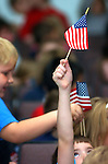 A boy holds his flag high during a Veterans Day ceremony at Montgomery  Elementary School in Montgomery, PA.