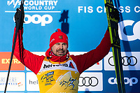 1st January 2020, Toblach, South Tyrol , Italy;  Sergey Ustiugov of Russia celebrates on the podium after the mens 15 km classic technique pursuit during Tour de Ski on January 1, 2020 in Toblach.