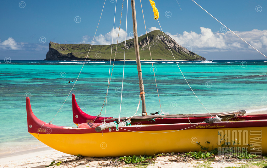 A brightly colored outrigger canoe lies in the foreground of this Waimanalo Beach scene in Windward O'ahu. Behind it, residents and tourists alike explore the reef of Waimanalo Bay, with Rabbit Island in the distance.