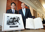 AUSTRALIA, Canberra : Japanese Prime Minister Shinzo Abe (L) and Australian Prime Minister Tony Abbott (R) stand in front of the 1957 Agreement on Commerce between Australia and Japan, at Parliament House in Canberra on July 8, 2014. Defence ties are set to take centre stage when Australia plays host to Japanese Prime Minister Shinzo Abe this week, as the two countries look set to strengthen their relationship through annual leaders' meetings. AFP PHOTO / Mark GRAHAM