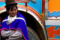 A Guambiano girl waits in front of a colorfully painted Chiva bus during the traditional Indian market in Silvia, Colombia, 8 April 2004. The Guambiano, a South American Indian tribe, live in the southwestern corner of Colombia. There are about 20.000 of Guambianos living in communities close to their capital town of Silvia. Guambianos are traditionally agricultural people. Since the Spanish conquest they have been gradually evicted from their original fertile lands up to the cold, rainy mountains. In spite of the permanent pressure by Colombian society, the Guambiano Indians still speak their original language, keep their colorful clothes and maintain their nature based religious customs.