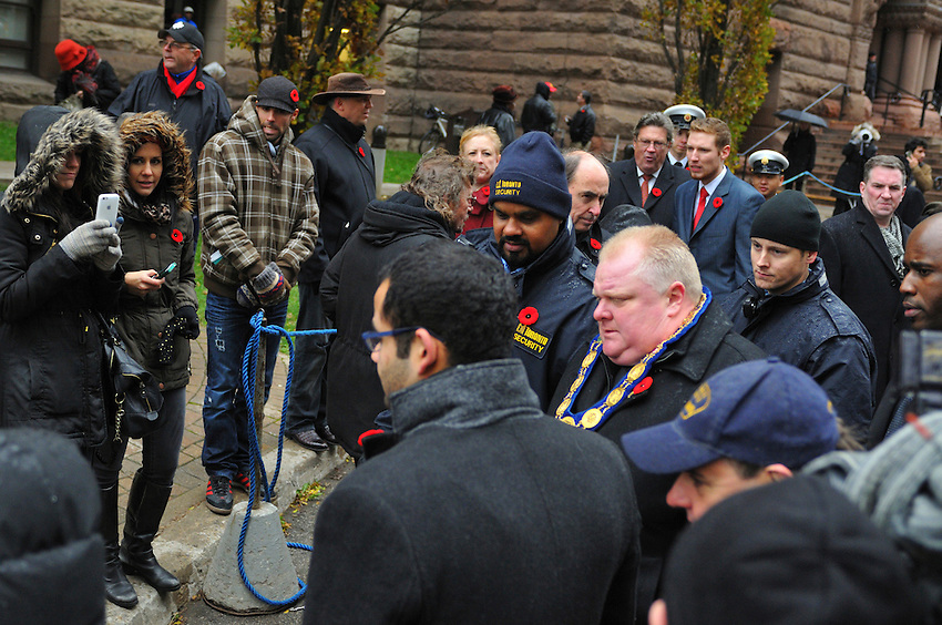 November 11, 2013, having just attended Remembrance Day Ceremonies and delivered a commemorative address at The Cenotaph of Old City Hall, at Toronto, Ontario, Canada, Mayor Rob Ford is beset by throngs of reporters.