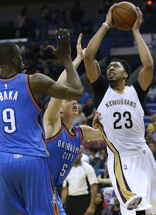 New Orleans Pelicans forward Anthony Davis (23) drives against Oklahoma City Thunder forward Kyle Singler (5) and forward Serge Ibaka (9) during an NBA basketball game Thursday, Feb. 25, 2016, in New Orleans. (AP Photo/Jonathan Bachman)