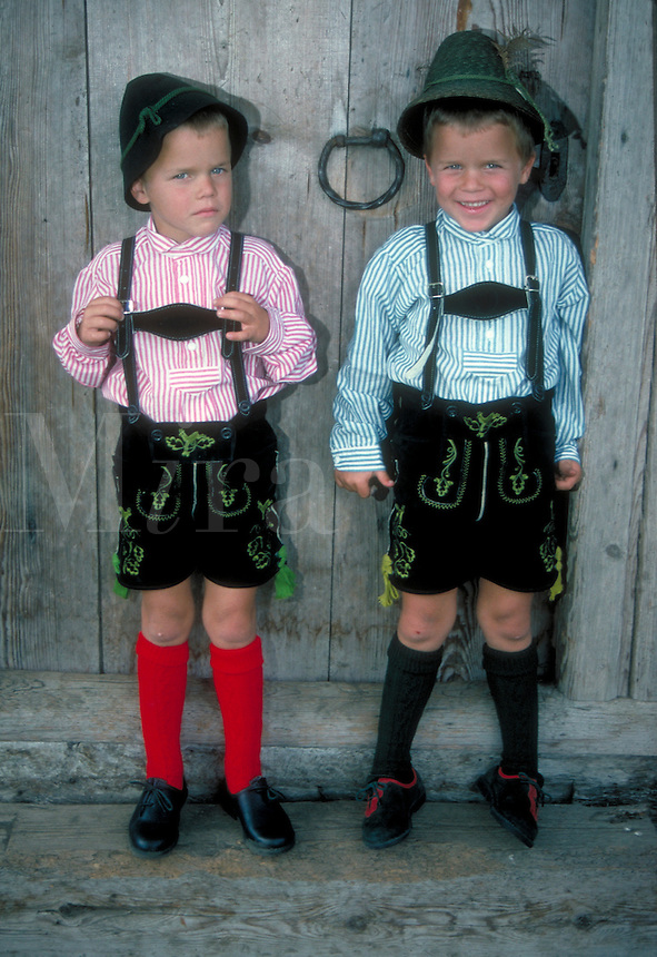 Two young boys in traditional Bavarian dress - lederhosen, Tyrollean hats, knee socks, and striped shirts. Paul and Tom. Germany.