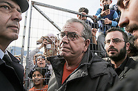 Pictured: Migration Minister Yiannis Mouzalas at the gate of the camp Monday 06 February 2017<br /> Re: Scuffles between migrants and police broke out during a visit by Immigration Policy Minister Yiannis Mouzalas at the Elliniko migrant camp located in the former airport in the outskirts of Athens, Greece.