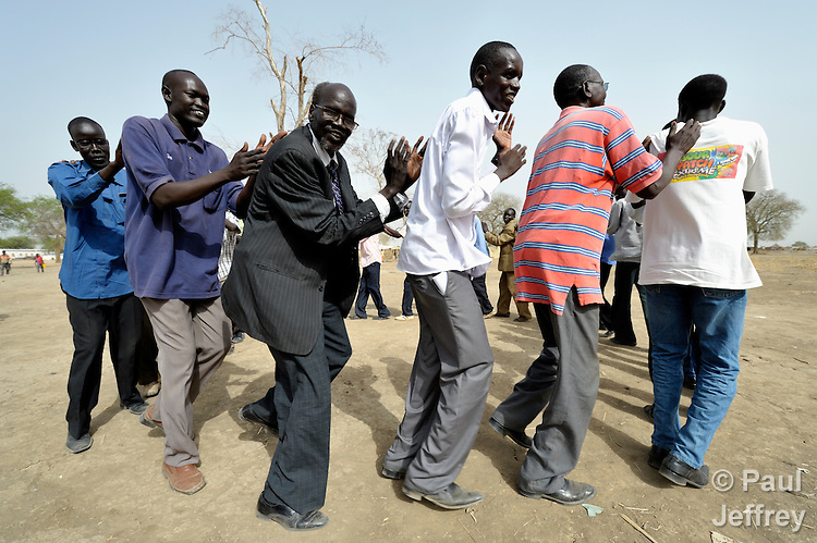 Displaced school teachers dance during a ceremony ending a special training course in Agok, a town in the contested Abyei region where tens of thousands of people fled in 2011 after an attack by soldiers and militias from the northern Republic of Sudan on most parts of Abyei. Although the 2005 Comprehensive Peace Agreement called for residents of Abyei--which sits on the border between Sudan and South Sudan--to hold a referendum on whether they wanted to align with the north or the newly independent South Sudan, the government in Khartoum and northern-backed Misseriya nomads, excluded from voting as they only live part of the year in Abyei, blocked the vote and attacked the majority Dinka Ngok population. The African Union has proposed a new peace plan, including a referendum to be held in October 2013, but it has been rejected by the Misseriya and Khartoum. The Catholic parish of Abyei, with support from Caritas South Sudan and other international church partners, has maintained its pastoral presence among the displaced and assisted them with food, shelter, and other relief supplies. The teachers (a separate circle of women teachers was nearby) received training from members and volunteers of Solidarity with South Sudan, an international network of Catholic religious orders and congregations providing training in education, health care, and pastoral work in the world's newest country.