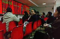People gather in Changsha stocks and securities exchange to look keep an eye on their investments..17-JAN-03
