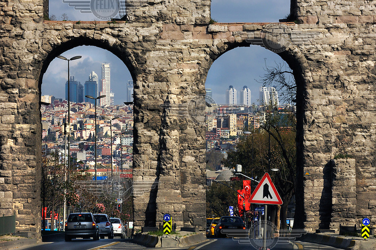 Highrise buildings rising on the fringes of the city through arches of the Roman Aqueduct of Valens.