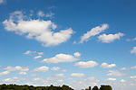 Fluffy cumulus clouds floating across blue sky above Suffolk, England, UK