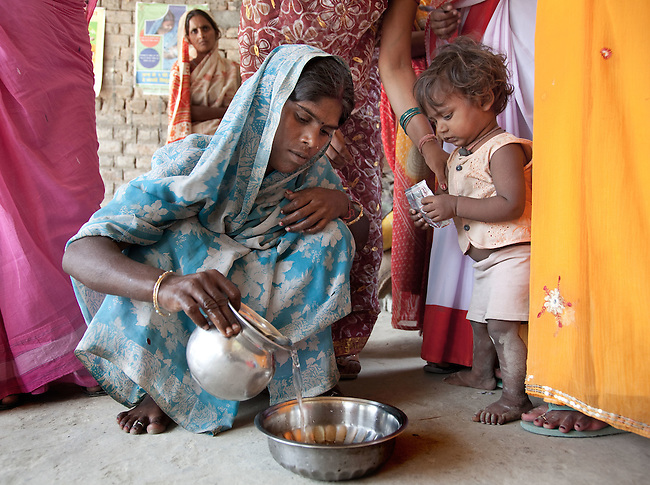 Bindu Devi mixes up some oral rehydration salts for her son Sahil Kumar (right) at the local Anganwadi health clinic at Bhagwanpuri Raiti village  where oral rehydration salts (ORS) and zinc tablets are given out to combat the sometimes fatal effects of diarrhea.The village located in Vaishali district outside Patna in Bihar, India has been rolling out the ORS and Zinc program as part of the IKEA Social Initiative to combat child mortality rates caused by diarrhea. It is proving to be very successful with education and support provided by local nursing staff, health activists  and program officers from UNICEF. The treatment is a 14 day course administering diluted oral rehydration salts and a zinc tablet which is more effective than salts alone in combating the effects of severe diarrhea. Picture by Graham Crouch/UNICEF