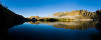 Panoramic Photo of Misty Dawn Reflections in a Calm Lake Moke, Queenstown, South Island, New Zealand. Lake Moke, 10km from Queenstown is both a stunning lake and a department of conservation campsite (DOC campsite) with access for both caravans and campervans. In the early mornings Lake Moke is often perfectly still providing picture perfect reflections of the surrounding hills and mountains in the water. The combination of a fabulous golden hour as the sun rose over the hills, the morning mist lifting from the lake, and the rich, orange, autumn trees made this nights camping at the Lake Moke department of conservation campsite (DOC campsite) particularly special.