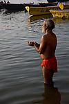 Indian man bathing and making offerings at the Ganges River in Varanasi, Uttar Pradesh, India