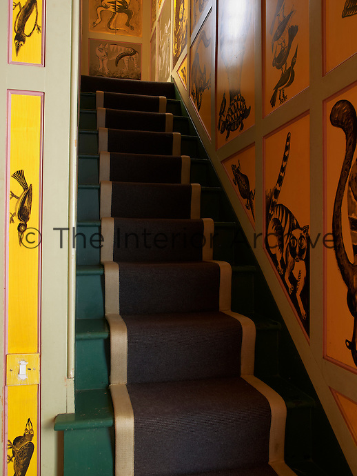 A series of painted panels featuring birds and animals lines the walls of the staircase