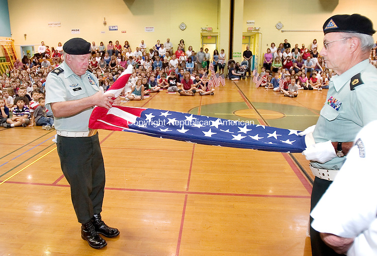 TORRINGTON, CT. 15 June 2010-061510SV04--From left, Sgt. Major Len Dube and Master Sgt. Steve Kovaleski of the Final Honor Guard Squad show students how to fold an American flag during Flag Day ceremonies at East Elementary School in Torrington Monday.<br /> Steven Valenti Republican-American