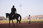 Policeman on horse patrols Kano football stadium..The implementation of Islamic Sharia Law across the twelve northern states of Nigeria, centres upon Kano, the largest Muslim Husa city, under the feudal, political and economic rule of the Emir of Kano. Islamic Sharia Law is enforced by official state apparatus including military and police, Islamic schools and education, plus various volunteer Militia groups supported financially and politically by the Emir and other business and political bodies. Fanatical Islamic Sharia religious traditions  are enforced by the Hispah Sharia police. Deliquancy is controlled by the Vigilantes volunteer Militia. Activities such as Animist Pagan Voodoo ceremonies, playing music, drinking and gambling, normally outlawed under Sharia law exist as many parts of the rural and urban areas are controlled by local Mafia, ghetto gangs and rural hunters. The fight for control is never ending between the Emir, government forces, the Mafia and independent militias and gangs. This is fueled by rising petrol costs, and that 70% of the population live below the poverty line. Kano, Kano State, Northern Nigeria, Africa