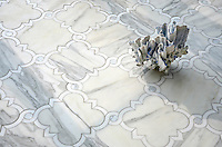 Atticus, a waterjet stone mosaic, shown in honed Calacatta, polished Thassos and Shell, is part of the Parterre Collection by Sara Baldwin for New Ravenna.<br />
