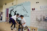 Jasmine Johnson, left, and Aliya Ali Abdelqader, right, both eleven year old   middle school students, clean up after painting a mural against hate at a middle school in the borough of Brooklyn in New York on Sunday, March 25, 2012.  The mural was part of the Anti-Defamation League No Place for Hate program.  (© Frances M. Roberts)