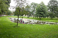 Polish children playing by city pond.  Paderewski Park Rzeczyca Central Poland
